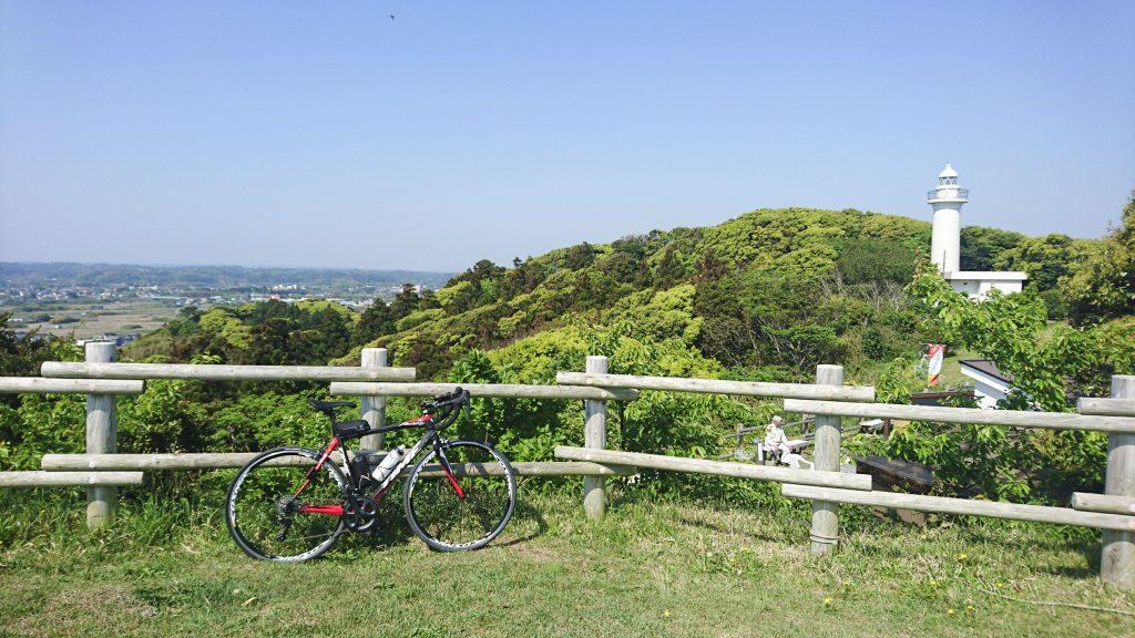 高台から青空とロードバイクと灯台