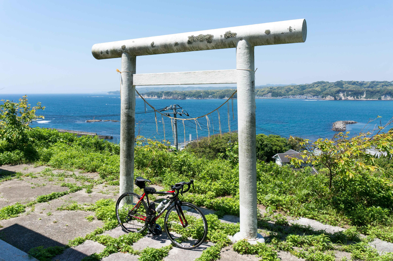 海を背景に鳥居と自転車