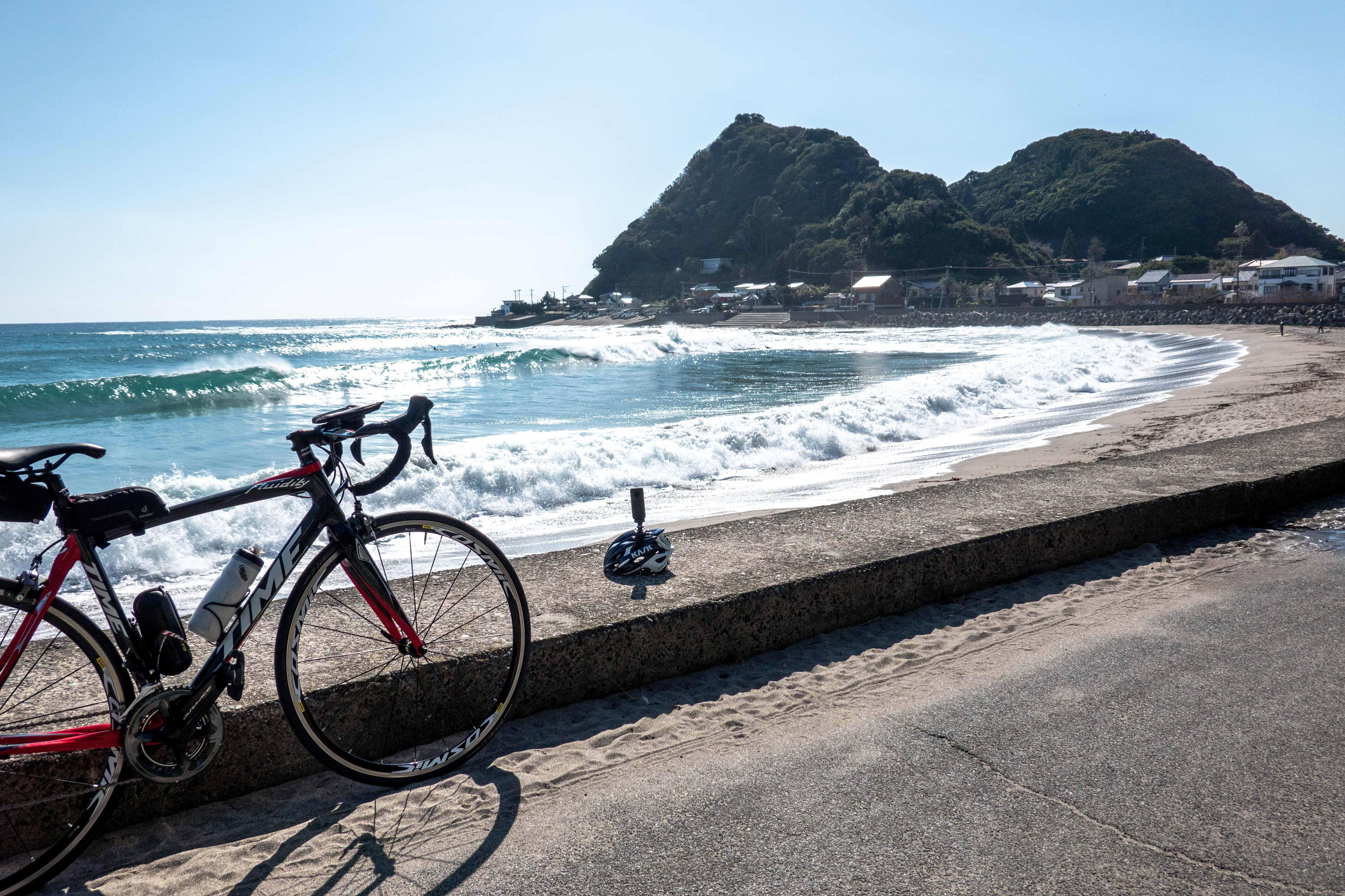 青空とロードバイクと砂浜とヘルメットが並ぶ