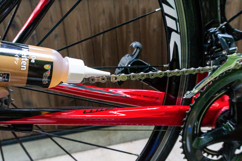 自転車のチェーンにオイルを注油している